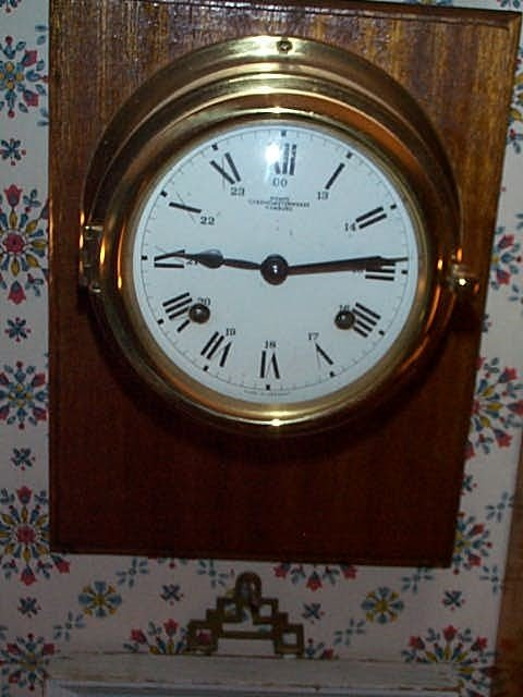 21: German ship's clock mounted on a wood plaque signed