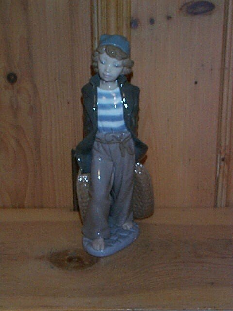 2: Lladro figurine depicting a young sailor boy carryin