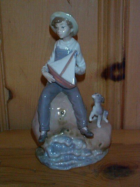 8: Lladro figurine depicting a young boy sitting on a r