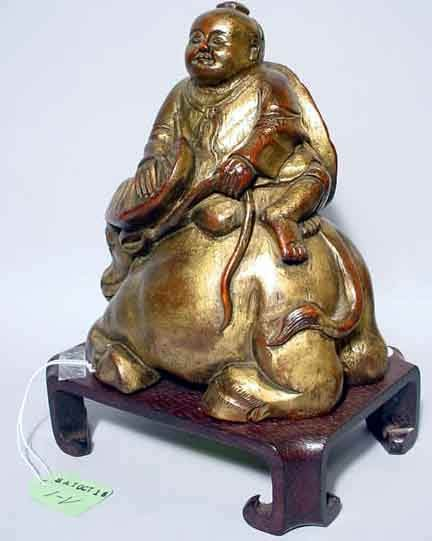 1V: SMALL CARVED AND GILDED FIGURE OF A CHILD SITTING O