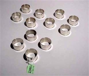 12 STERLING SILVER NAPKIN RINGS, with fol