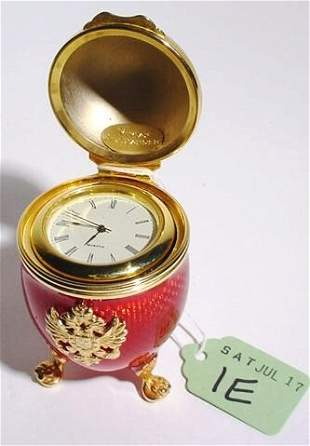 GILT METAL AND ENAMEL EGG FORM CLOCK ON STAND