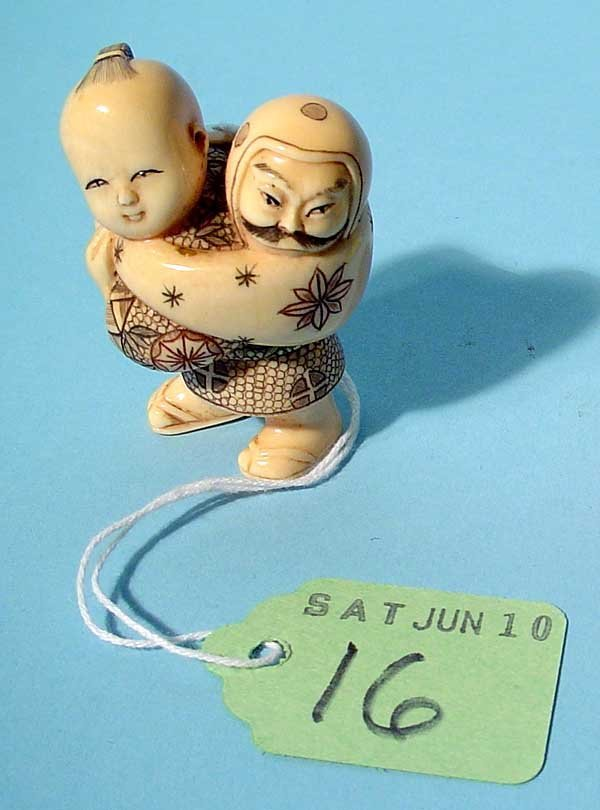 16: CARVED AND TINTED IVORY NETSUKE OF A STANDING BOY C