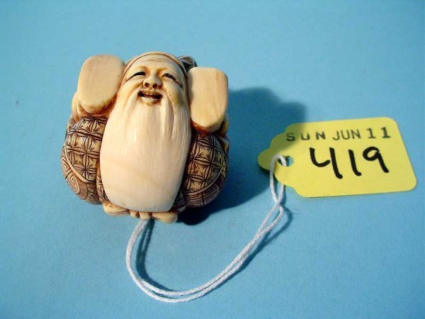 419: WELL-CARVED AND TINTED IVORY NETSUKE OF A BEARDED