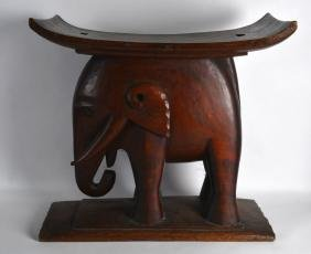 A LARGE CARVED HARDWOOD ETHNIC STOOL in the form of a