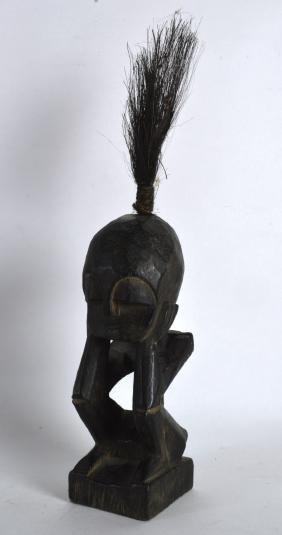 AN AFRICAN CARVED WOOD FIGURE modelled with hands upon