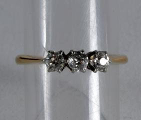 AN ANTIQUE THREE STONE DIAMOND AND YELLOW GOLD RING.