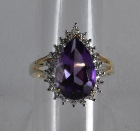 A 9CT GOLD PEAR SHAPED AMETHYST AND DIAMOND RING.