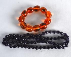 A CARVED AMETHYST NECKLACE together with an amber