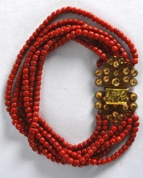 AN 18CT YELLOW GOLD AND CARVED RED CORAL NECKLACE. 226