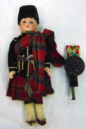A SCOTTISH BISQUE HEAD DOLL, together with a tin plate