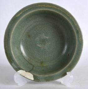 A CHINESE YUAN/MING DYNASTY CELADON DISH decorated in
