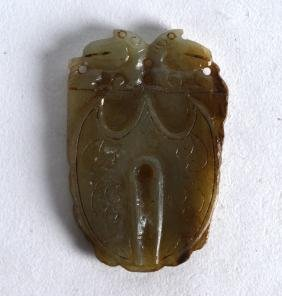 A CHINESE CARVED JADE AMULET with twin mask head