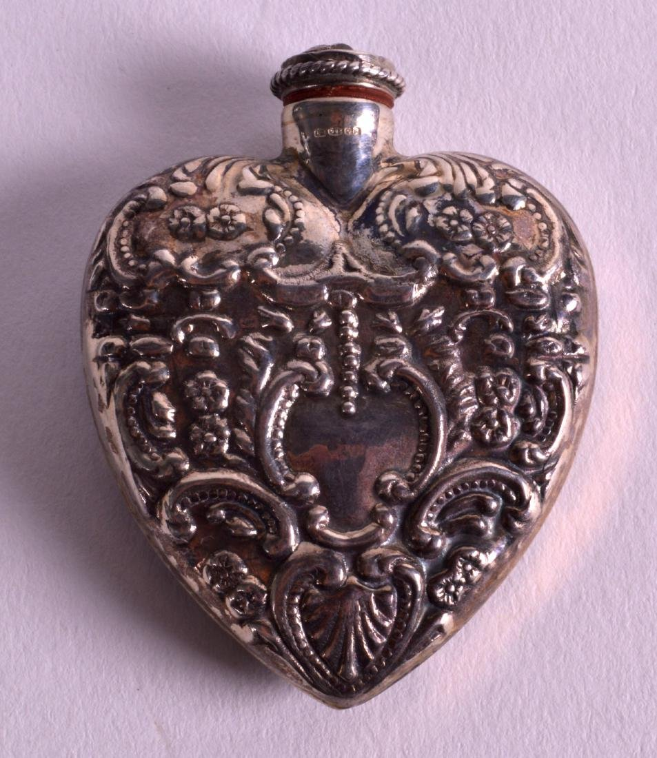 A SILVER HEART SHAPED SCENT BOTTLE decorated in relief