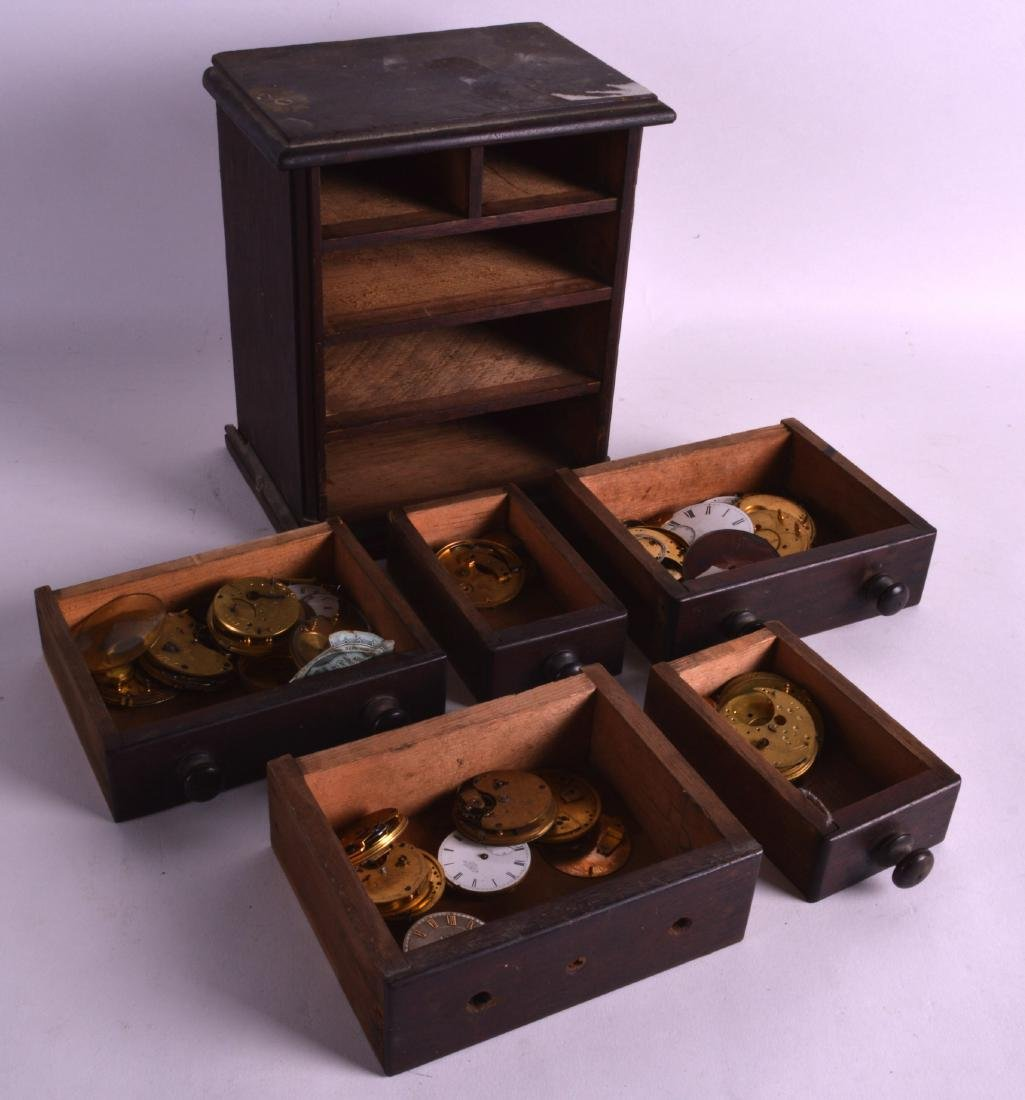 A MINIATURE CHEST OF DRAWERS containing numerous clock
