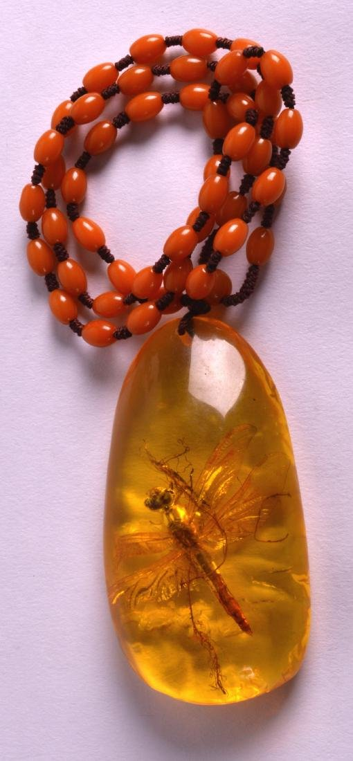 AN EARLY 20TH CENTURY CHINESE CARVED AMBER PENDANT with