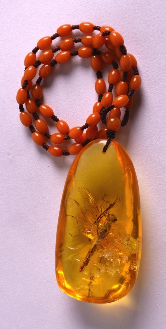 AN EARLY 20TH CENTURY CHINESE CARVED AMBER PENDANT with - 2
