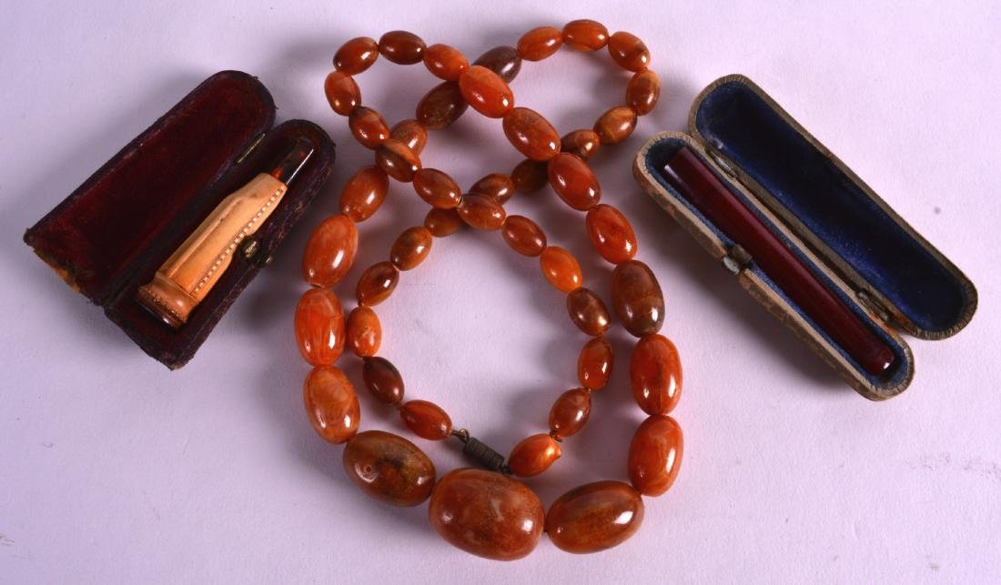 A SET OF EARLY 20TH CENTURY CARVED AMBER BEADS together