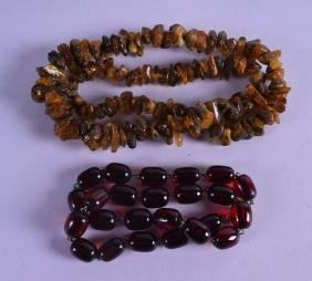 TWO CARVED AMBER NECKLACES. (2)