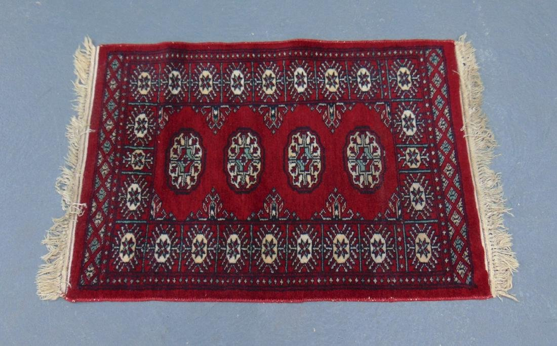 A SMALL RED GROUND PERSIAN RUG, decorated with MOTIFS