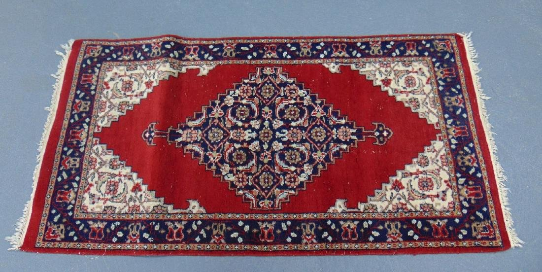 A SMALL RED GROUND PERSIAN RUG, decorated with central