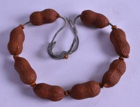 AN UNUSUAL CHINESE CARVED NUT BRACELET.