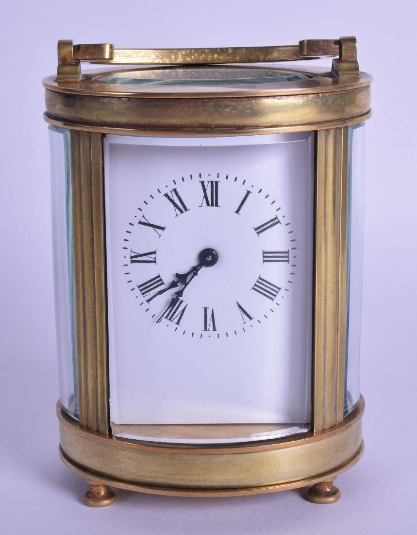 A FRENCH BRASS OVAL CARRIAGE CLOCK with white enamel