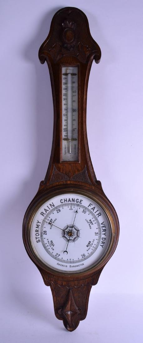 A LATE VICTORIAN/EDWARDIAN CARVED OAK ANEROID BAROMETER