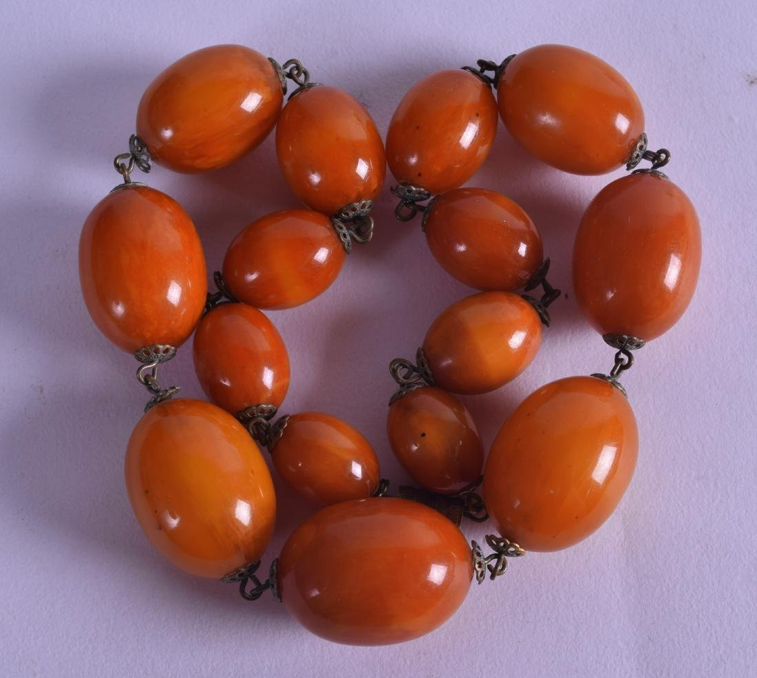 AN EARLY 20TH CENTURY CARVED HONEY AMBER NECKLACE of