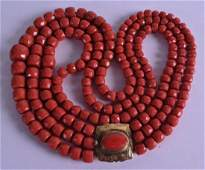 AN 18CT YELLOW GOLD MOUNTED TRIPLE STRAND CORAL