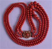 AN 18CT YELLOW GOLD TRIPLE STRAND CORAL NECKLACE. 78