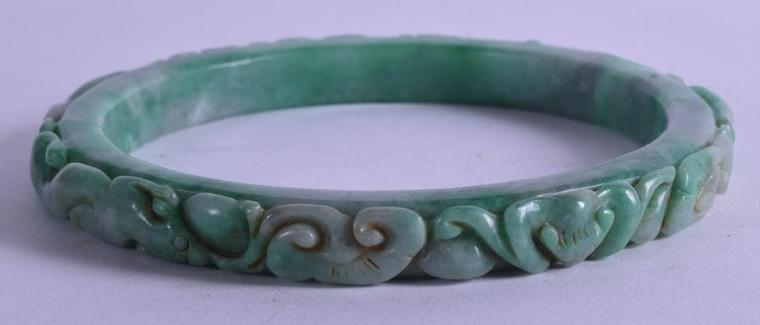 A LARGE CHINESE CARVED JADEITE ARM BANGLE decorated