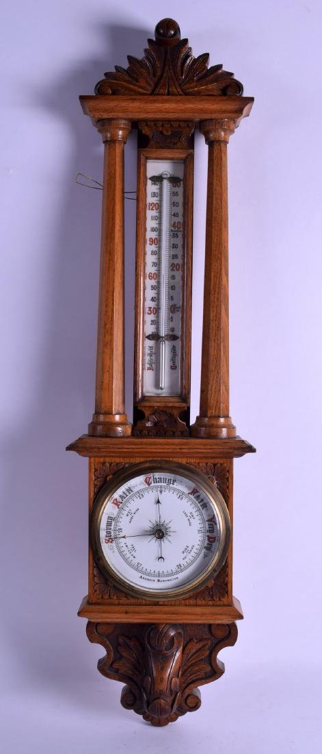 A LATE VICTORIAN/EDWARDIAN OAK ANEROID BAROMETER. 75 cm