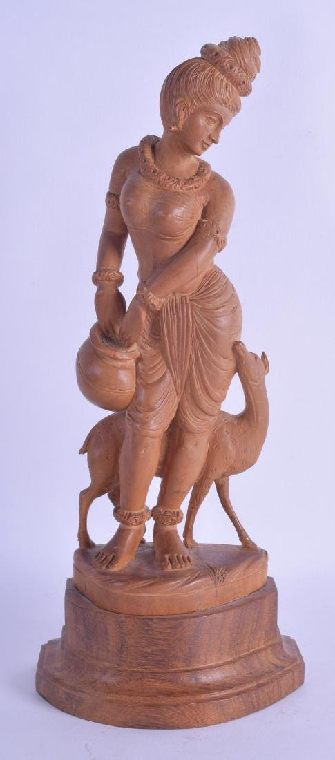 AN EARLY 20TH CENTURY INDIAN CARVED SANDALWOOD FIGURE