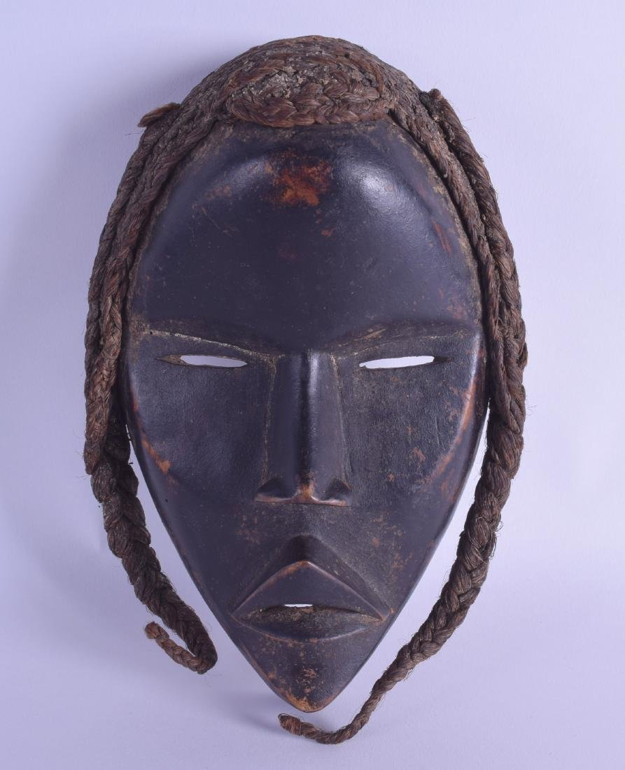 AN AFRICAN TRIBAL CARVED HARDWOOD FEMALE MASK with