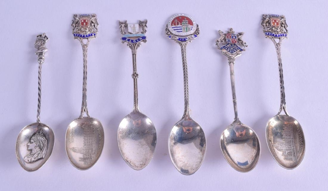 A SET OF FOUR SILVER AND ENAMEL SPOONS together with
