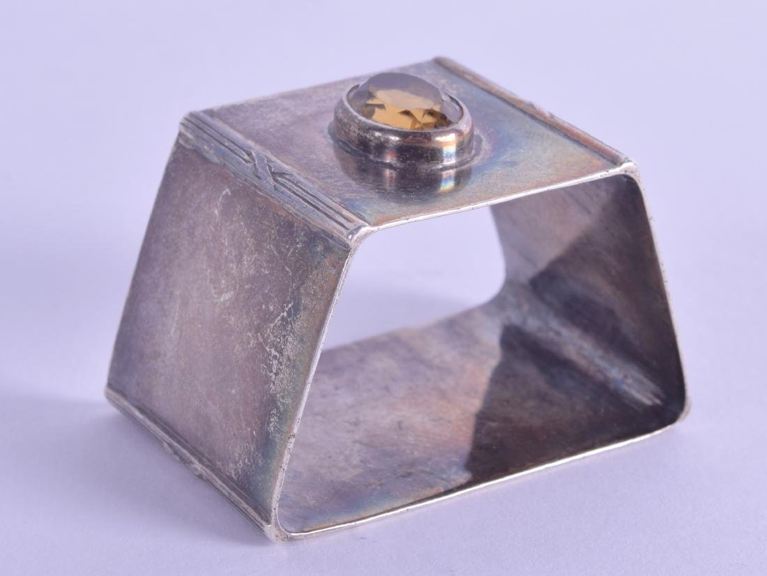 AN UNUSUAL EDWARDIAN SILVER AND CITRINE NAPKIN RING.