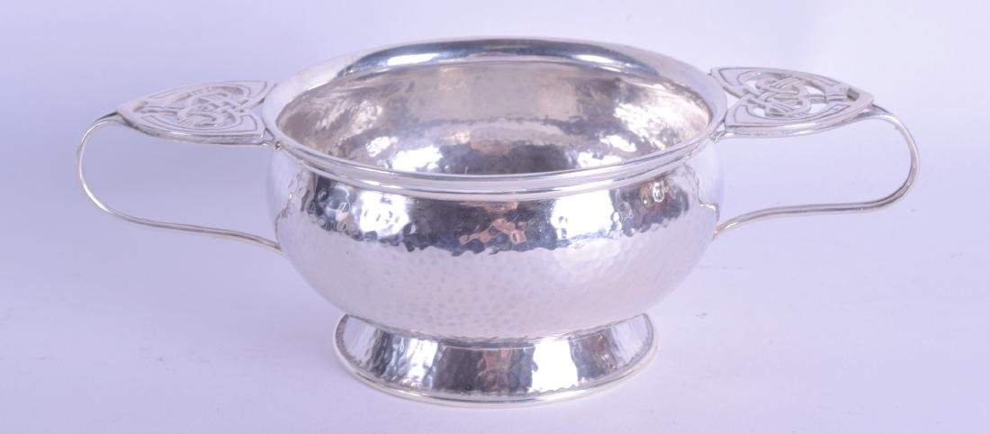 AN ART NOUVEAU TWIN HANDLED SILVER HAMMERED BOWL.