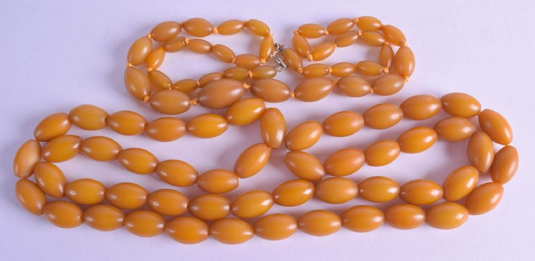 TWO EARLY 20TH CENTURY AMBER TYPE NECKLACES. 98 cm & 58