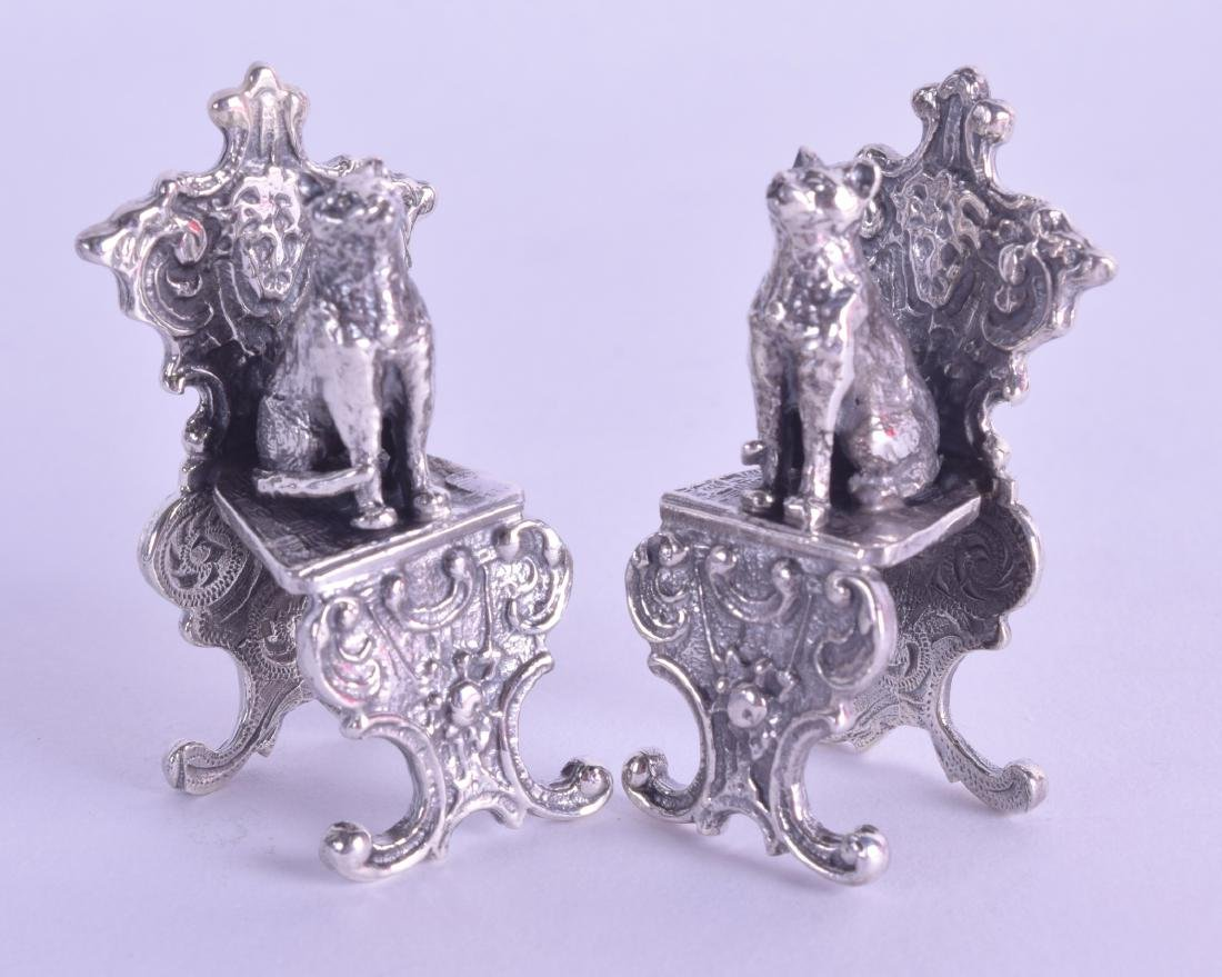 A PAIR OF NOVELTY SILVER CHAIRS surmounted with cats.