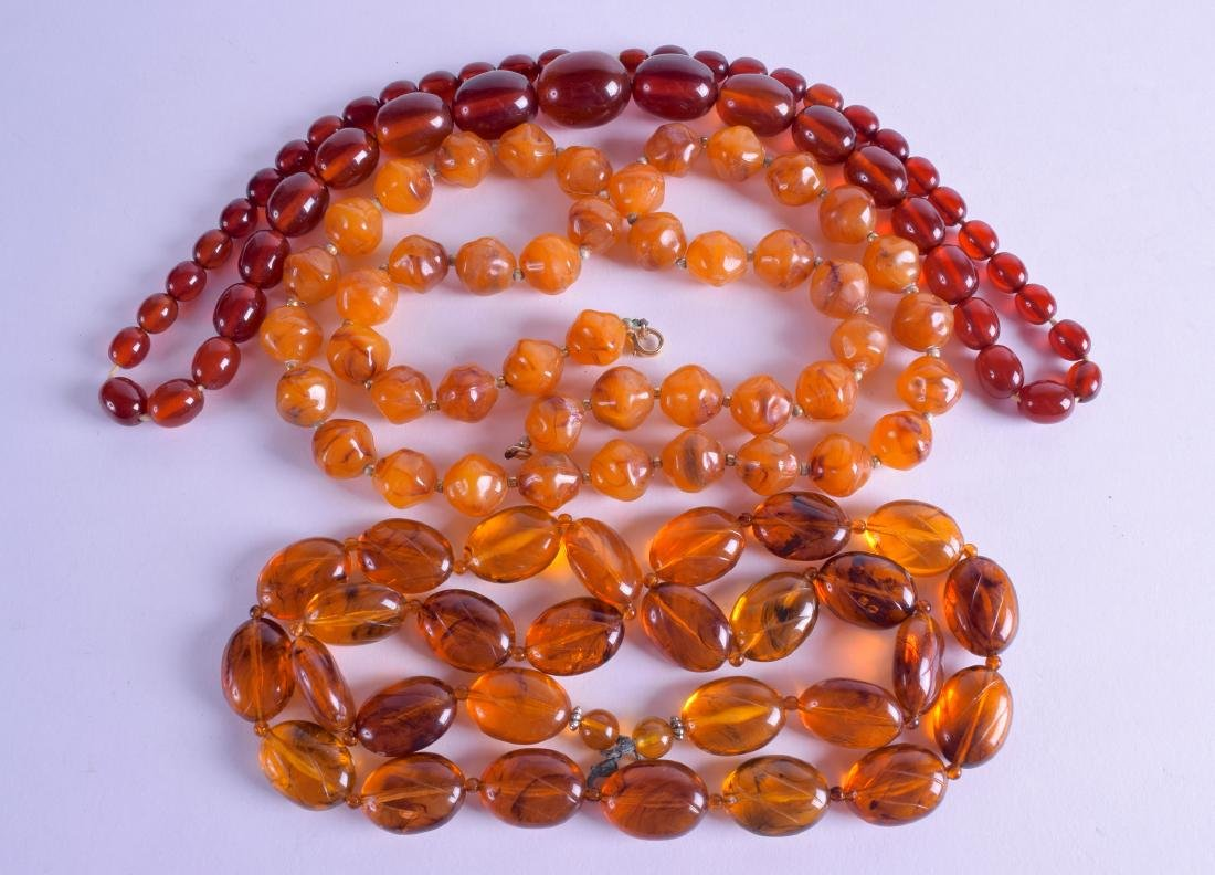 A GROUP OF THREE AMBER TYPE NECKLACES. 82 cm, 64 cm &