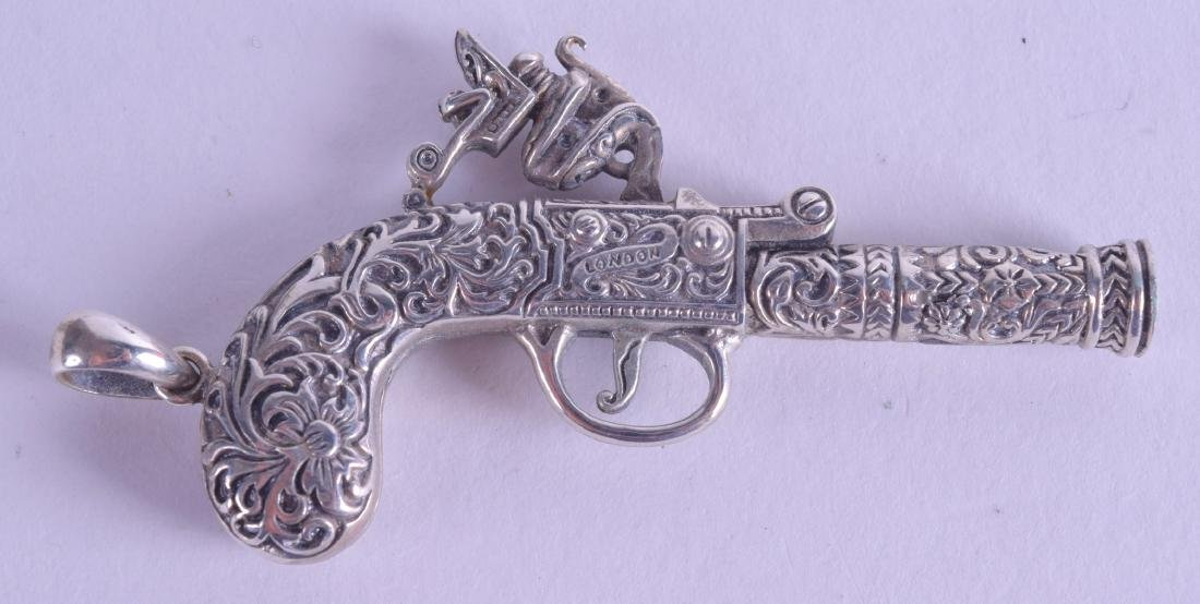 A NOVELTY SILVER PISTOL WHISTLE.