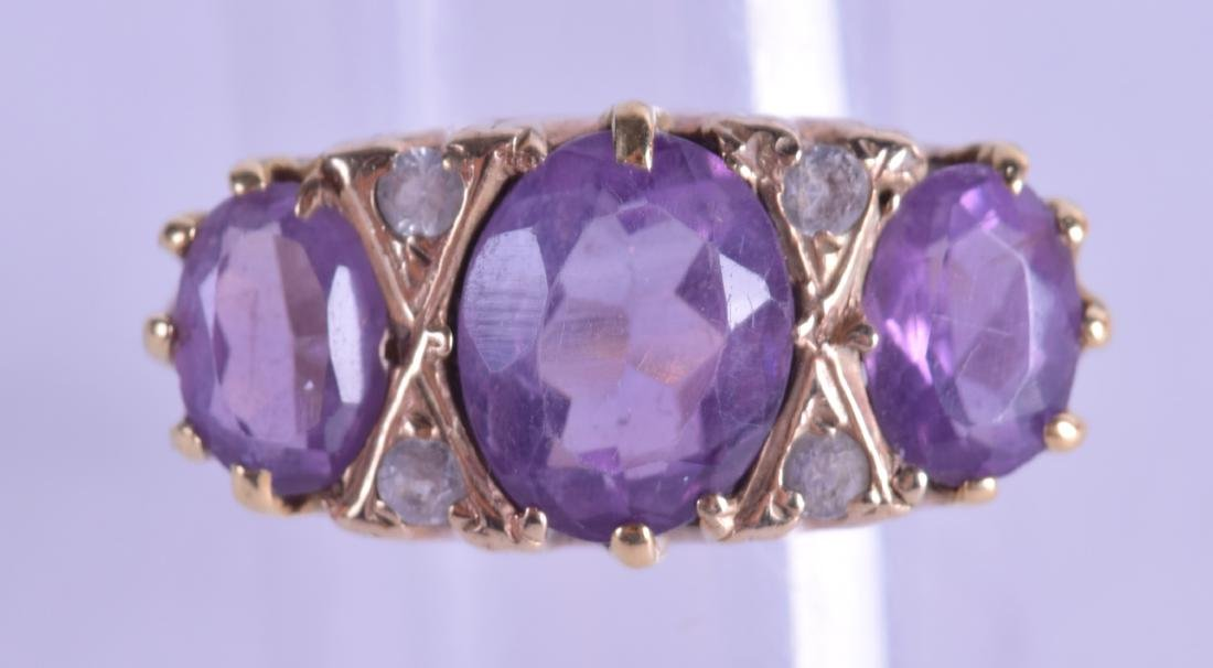 AN ANTIQUE 9CT GOLD AND TRIPLE AMETHYST RING. Size P/Q.