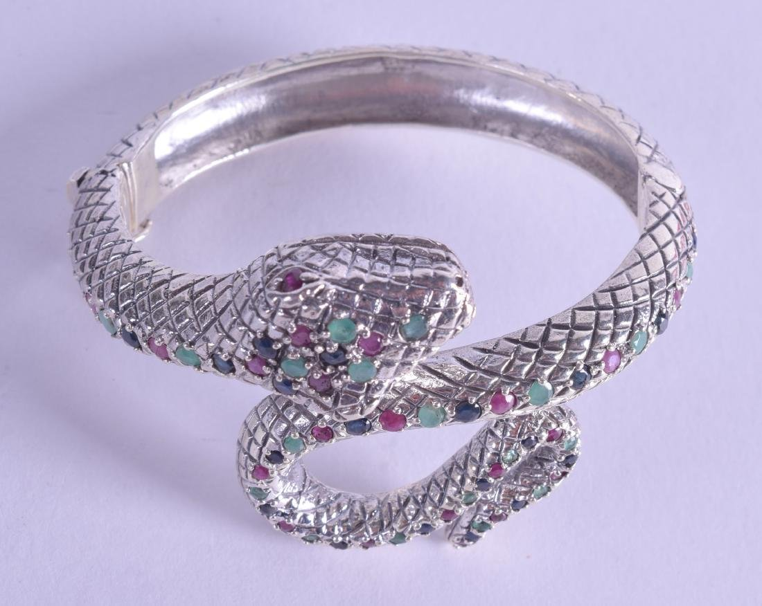 A SILVER EMERALD RUBY AND SAPPHIRE SNAKE BANGLE.