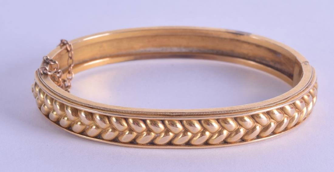AN ANTIQUE 15CT YELLOW GOLD LADIES HINGED BANGLE. 15.4
