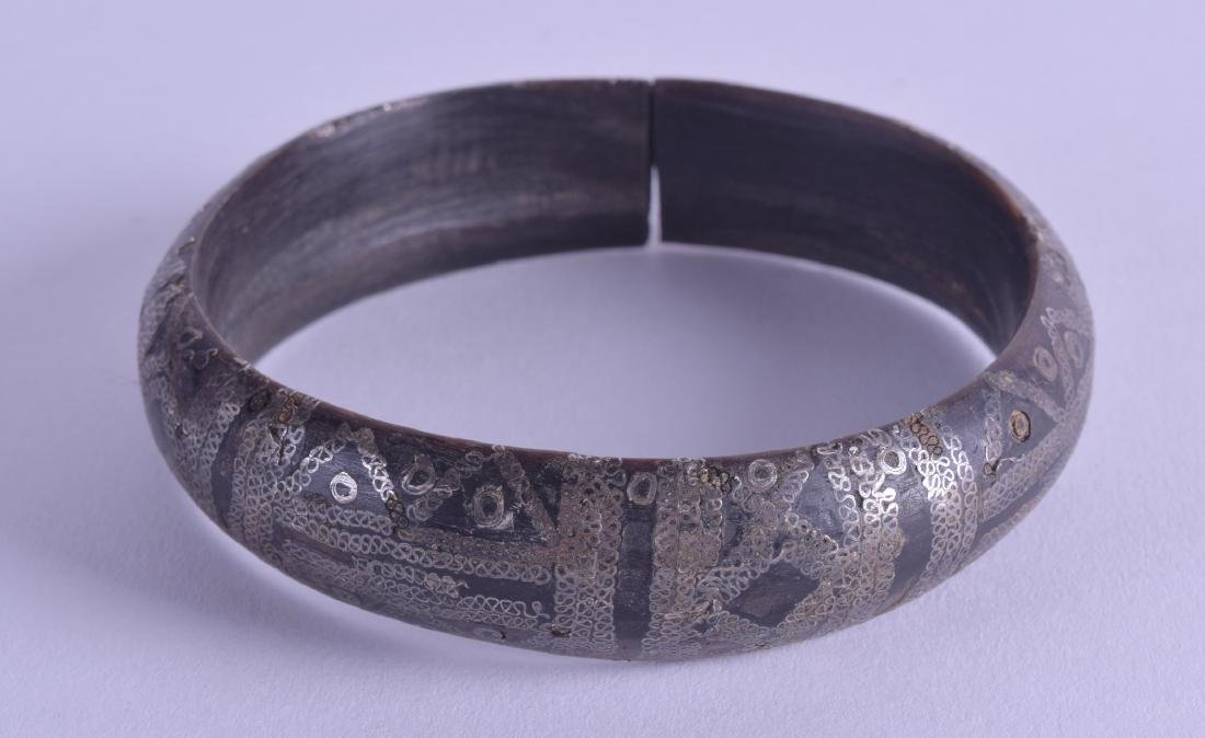 AN 18TH/19TH CENTURY SILVER INLAID EASTERN HORN BANGLE.