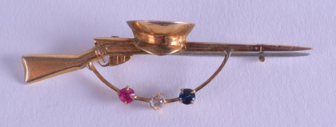 AN EDWARDIAN 9CT GOLD DIAMOND SAPPHIRE AND RUBY GUN