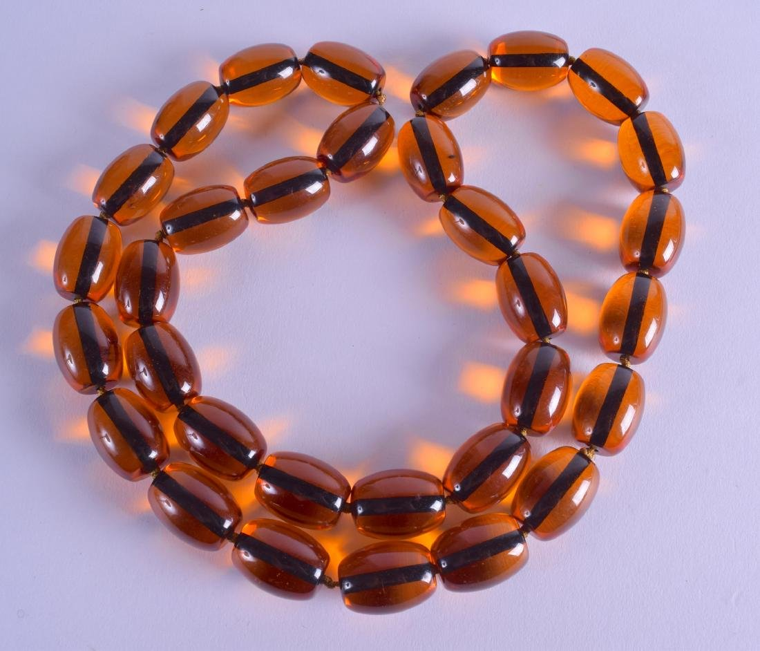 A LONG AMBER TYPE NECKLACE. 80 cm long overall.