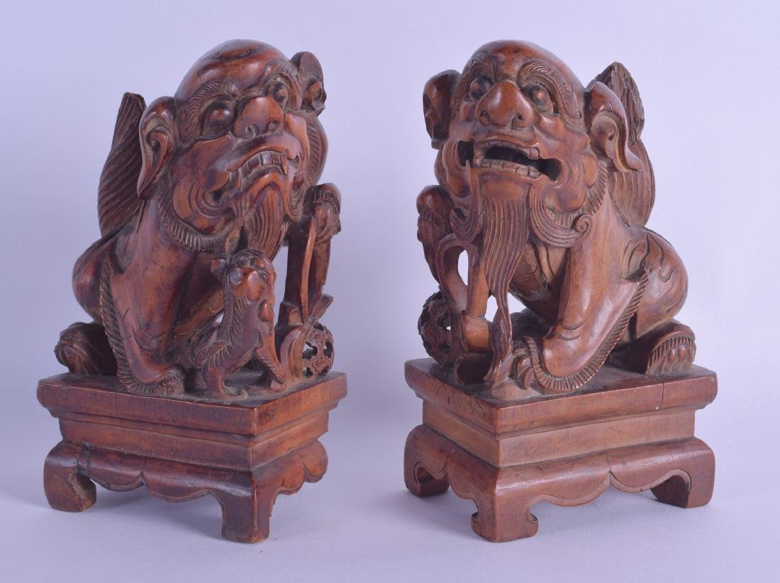 A PAIR OF CHINESE QING DYNASTY CARVED HARDWOOD DOGS OF