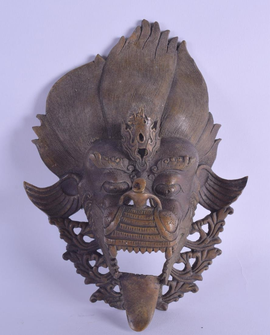 AN EARLY 20TH CENTURY TIBETAN BRONZE MASK HEAD in the